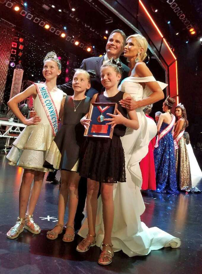 Mrs. Connecticut Izabela O'Brien, a Greenwich resident, poses with her husband Daniel and daughters  Yvette, Ireland and Alina (holding O'Brien's award for being a finalist) last month at the Mrs. America Pageant in Las Vegas. Photo: Contributed Photo/