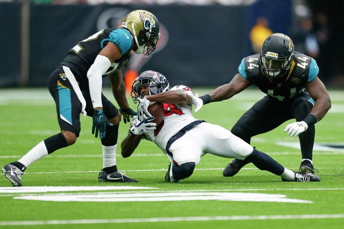Houston Texans running back Tyler Ervin (34) leans back for extra yards while flanked by Jacksonville Jaguars cornerback Aaron Colvin (22) and outside linebacker Myles Jack (44) in the second half as the Houston Texans lose to the Jacksonville Jaguars 29-7 at NRG Stadium Sunday, Sept. 10, 2017 in Houston.