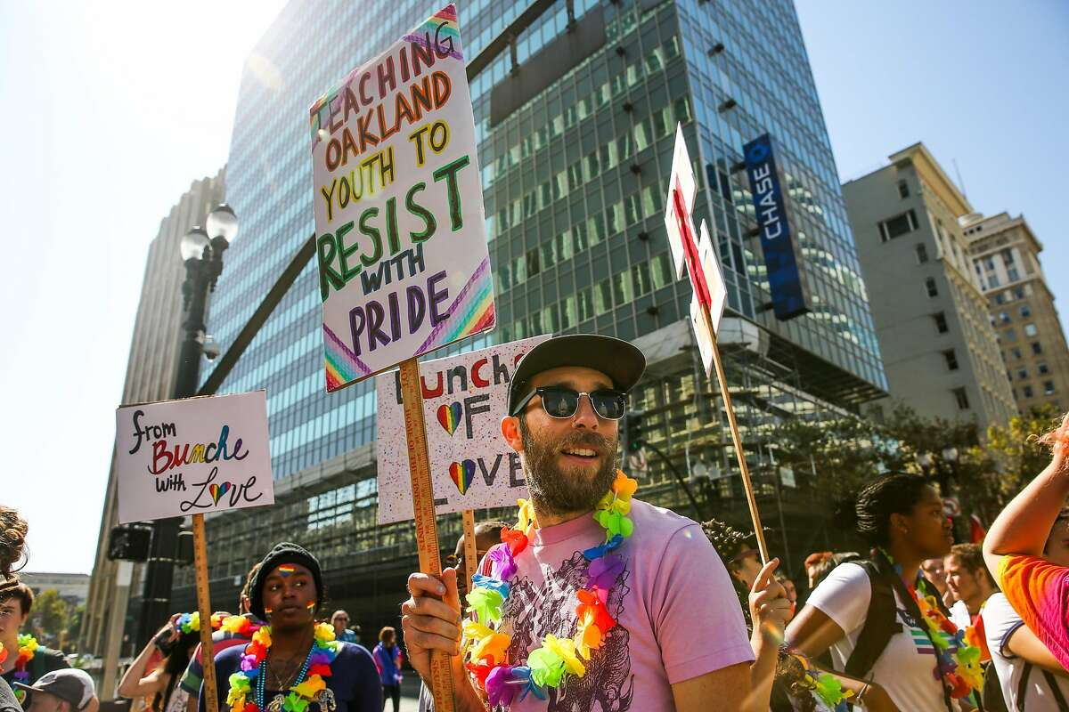 Sean Gleason (center) holds up a handmade sign while marching in the Oakland Pride Parade in Oakland, Calif., on Sunday, Sept. 10, 2017.