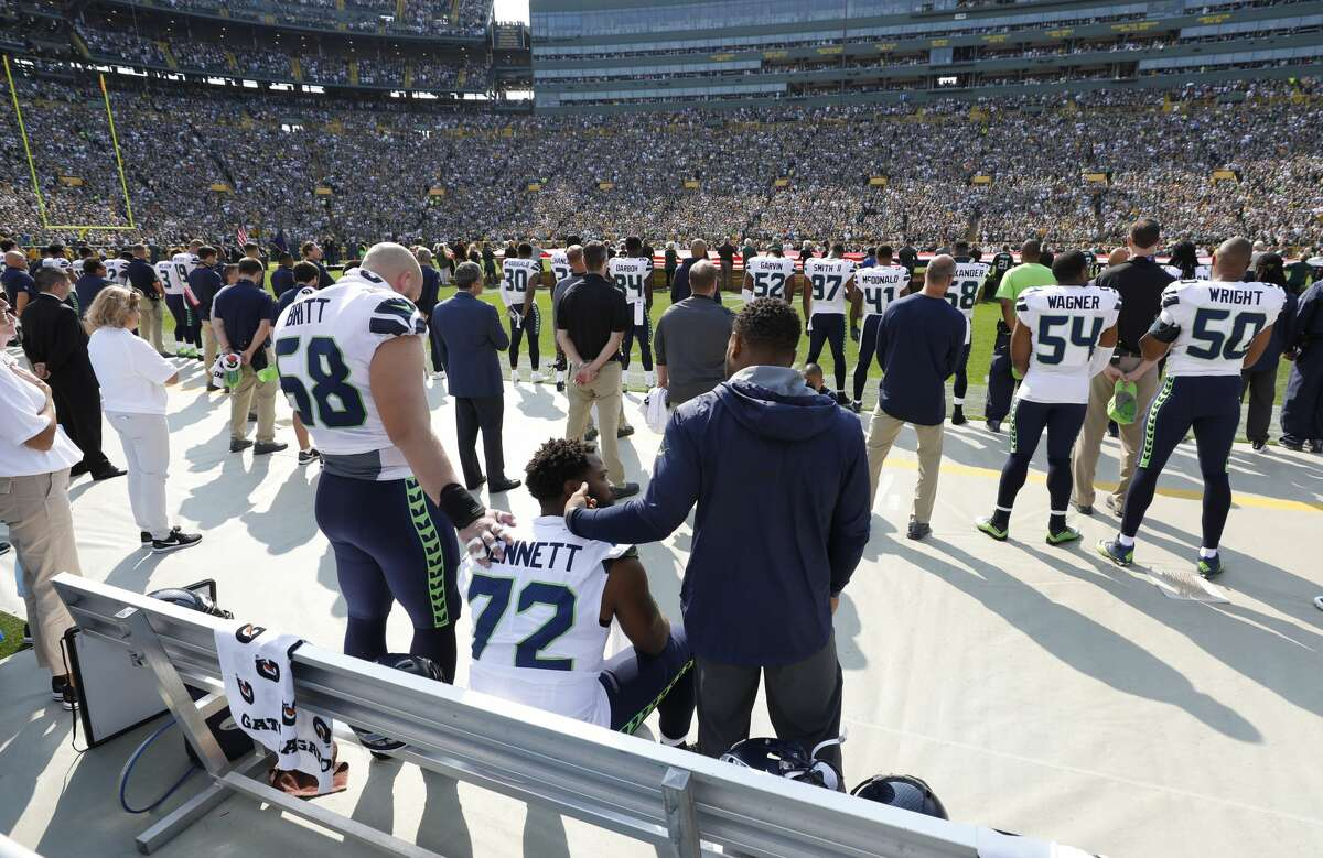 Seattle Seahawks' Michael Bennett remains seated on the bench during the national anthem before an NFL football game against the Green Bay Packers Sunday, Sept. 10, 2017, in Green Bay, Wis. (AP Photo/Jeffrey Phelps)