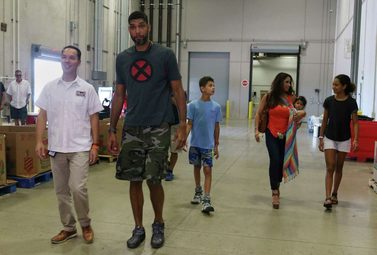 Former San Antonio Spurs player Tim Duncan walks with San Antonio Food Bank President/CEO Eric Cooper to a press conference announcing a hurricane relief mission to the U.S. Virgin Islands, Sunday, Sept. 10, 2017. Duncan will head the effort. Behind him are from left, his son, Draven, his girlfriend Vanessa Macias holding their daughter, Quill, and his daughter, Sydney.