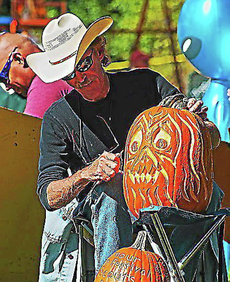 Craig Smith of Shelton carves a pumpkin at the 2015 Seymour Pumpkin Festival at French Memorial Park in Seymour. Photo: File Photo