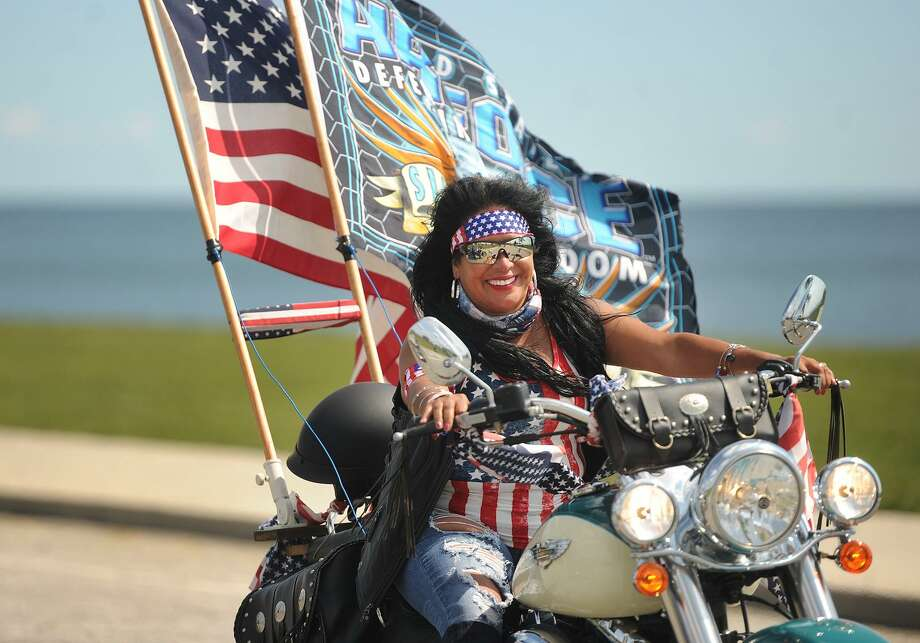Myrna Vivo, of Bridgeport, arrives in the city's Seaside Park on Sunday along with hundreds of motorcycle riders participating in the 2017 CT United Ride. Along with the American flag, Vivo's motorcycle sported an Air Force flag in honor of her children. Her son serves in the U.S. Air Force and her daughter is in the Air Force ROTC. Photo: Brian A. Pounds / Hearst Connecticut Media / Connecticut Post