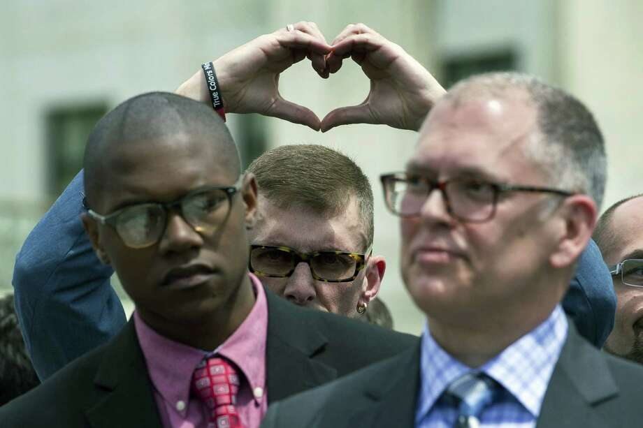 ap file photo Plaintiff Rev. Maurice Blanchard, of Louisville, Ky., makes heart with his hands behind plaintiff plaintiff James Obergefell of Ohio, right, as they stand outside of the Supreme Court in Washington. / FR170079 AP