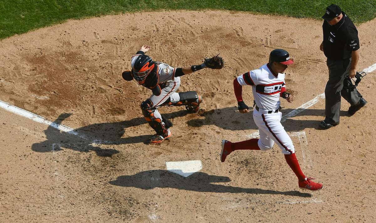 Chicago White Sox's Avisail Garcia, center, scores past San Francisco Giants catcher Buster Posey, left, as home plate umpire Eric Cooper looks on during the fifth inning of a baseball game in Chicago, Sunday, Sept. 10, 2017. (AP Photo/Matt Marton)