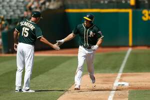OAKLAND, CA - SEPTEMBER 10: Matt Chapman #26 of the Oakland Athletics celebrates with third base coach Steve Scarsone #15 after hitting a solo home run in the fifth inning against the Houston Astros at Oakland Alameda Coliseum on September 10, 2017 in Oakland, California. (Photo by Lachlan Cunningham/Getty Images)