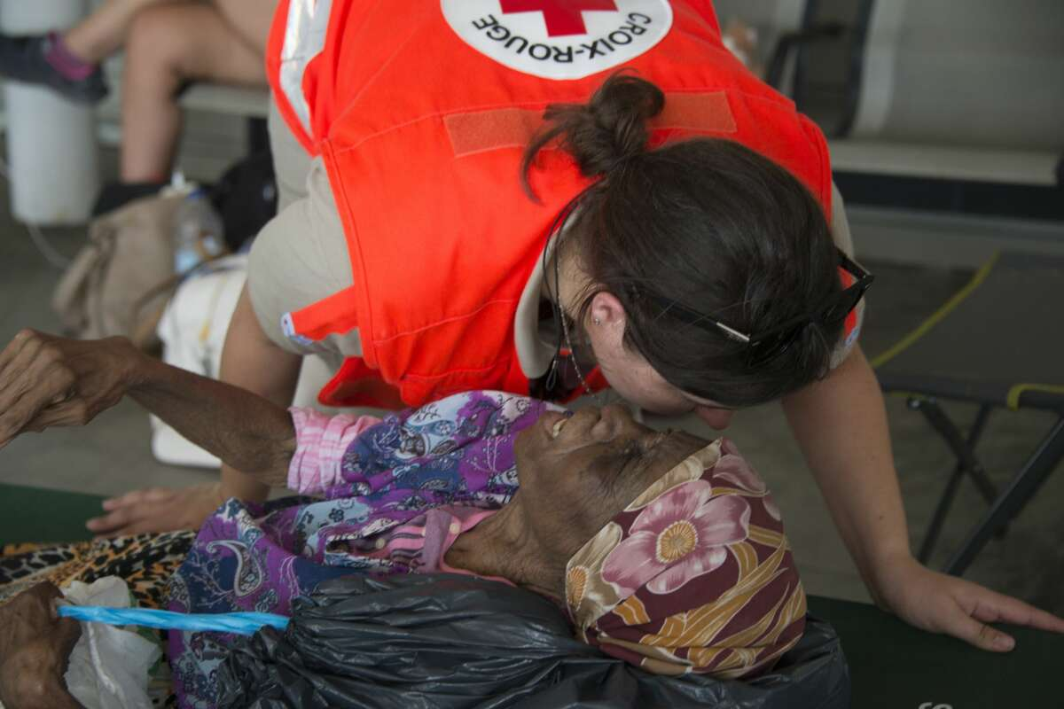 A woman from Saint Martin talks to a red cross worker in a shelter after being evacuated to Guadeloupe, the French Caribbean island, in Pointe-a-Pitre on September 10, 2017, after hurricane Irma passed. Ravaged by Hurricane Irma, Saint Martin and Saint Barts escaped a further battering by Jose, which had