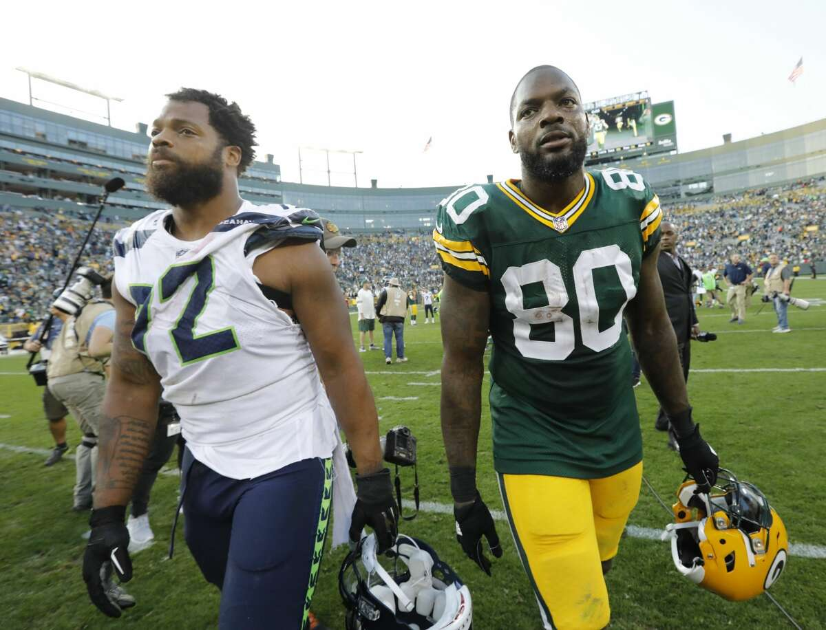 Green Bay Packers' Martellus Bennett (80) and brother Seattle Seahawks' Michael Bennett (72) walk off the field after an NFL football game Sunday, Sept. 10, 2017, in Green Bay, Wis. The Packers won 17-9. (AP Photo/Mike Roemer)