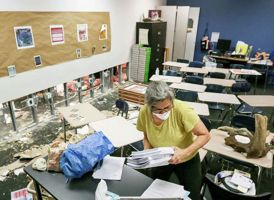 "Dee Julian, an AP English teacher from Kingwood High School, gathers teaching supplies from her former second-floor classroom at Kingwood High School, Friday, Sept. 8, 2017, in Humble. Teachers were given a 45-minute window to visit their classrooms and remove items, in order to take them to their new campus, Summer Creek High School. ""Getting books and highlighters,"" Julian said. ""They're for the kids.""  ( Jon Shapley  / Houston Chronicle ) Photo: Jon Shapley, Staff / © 2017 Houston Chronicle"