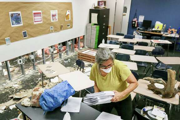 "Dee Julian, an AP English teacher from Kingwood High School, gathers teaching supplies from her former second-floor classroom at Kingwood High School, Friday, Sept. 8, 2017, in Humble. Teachers were given a 45-minute window to visit their classrooms and remove items, in order to take them to their new campus, Summer Creek High School. ""Getting books and highlighters,"" Julian said. ""They're for the kids.""  ( Jon Shapley  / Houston Chronicle )"