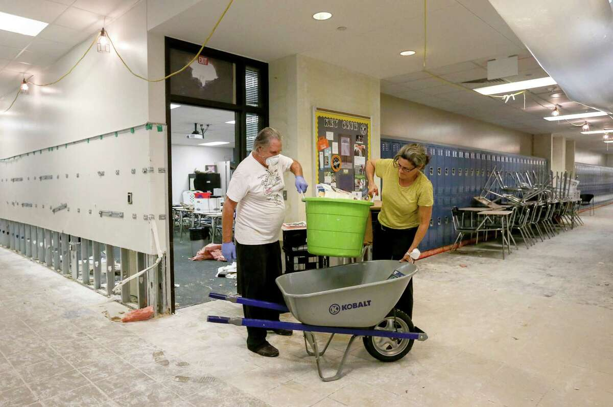 """Dee Julian, right, an AP English teacher from Kingwood High School, removes teaching supplies and a few personal items with the help of her husband, R. J., left, from her former second-floor classroom at Kingwood High School, Friday, Sept. 8, 2017, in Humble. Teachers were given a 45-minute window to visit their classrooms and remove items, in order to take them to their new campus, Summer Creek High School. """"Getting books and highlighters,"""" Julian said. """"They're for the kids."""" ( Jon Shapley / Houston Chronicle )"""