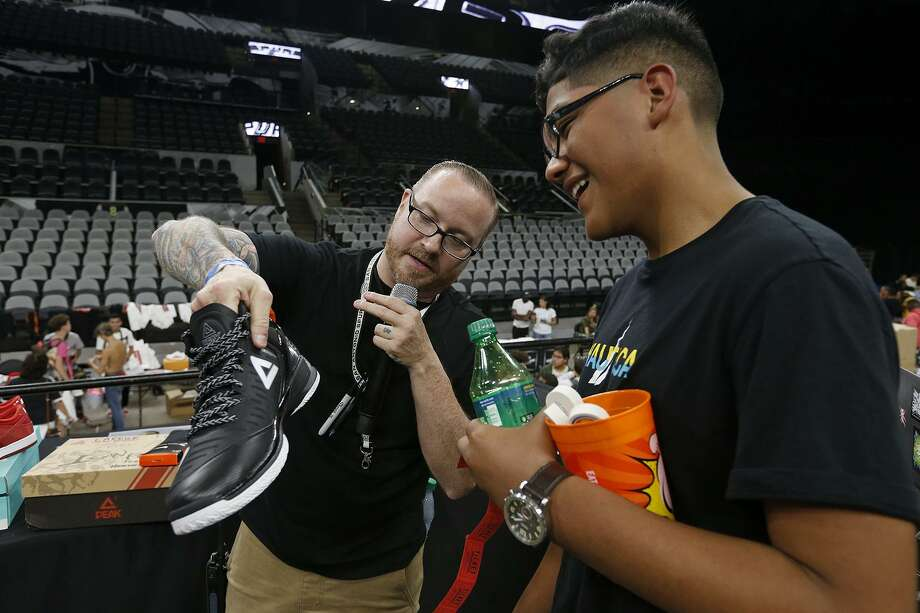 Emcee Norm Dawson gives raffle winner Victor Cornejo a pair of Peak Tony Parker Player Exclusive Sneakers. Photo: Edward A. Ornelas /San Antonio Express-News / © 2017 San Antonio Express-News