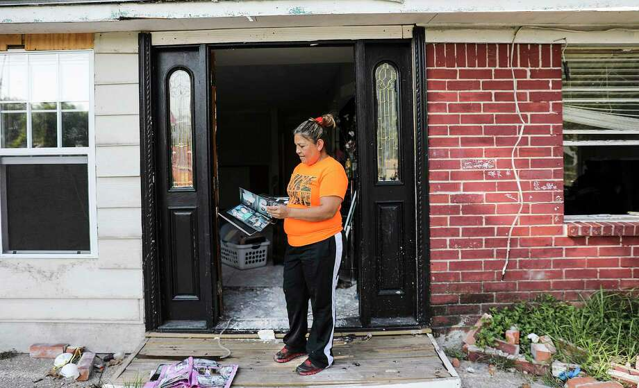 Evelyn Portillo holds a family photo album she found dry after her north Houston home flooded from Hurricane Harvey. Photographed on Saturday, Sept. 9, 2017. Photo: Elizabeth Conley, Houston Chronicle / © 2017 Houston Chronicle