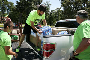 Darryl Solonka, of North Woodlands Area Church of Christ, loads water bottles into the bed of a pickup truck on Sunday at North Woodlands Area Church of Christ.