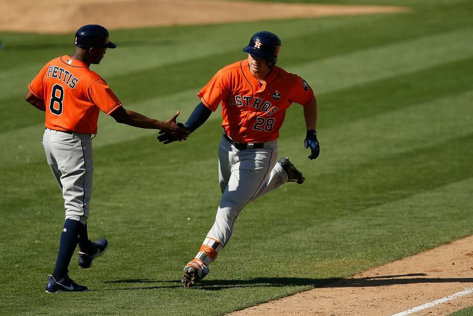 OAKLAND, CA - SEPTEMBER 10: J.D. Davis #28 of the Houston Astros celebrates with Third Base Coach Gary Pettis #8 of the Houston Astros after hitting a solo home run in the eighth inning against the Oakland Athletics at Oakland Alameda Coliseum on September 10, 2017 in Oakland, California. (Photo by Lachlan Cunningham/Getty Images) Photo: Lachlan Cunningham/Getty Images