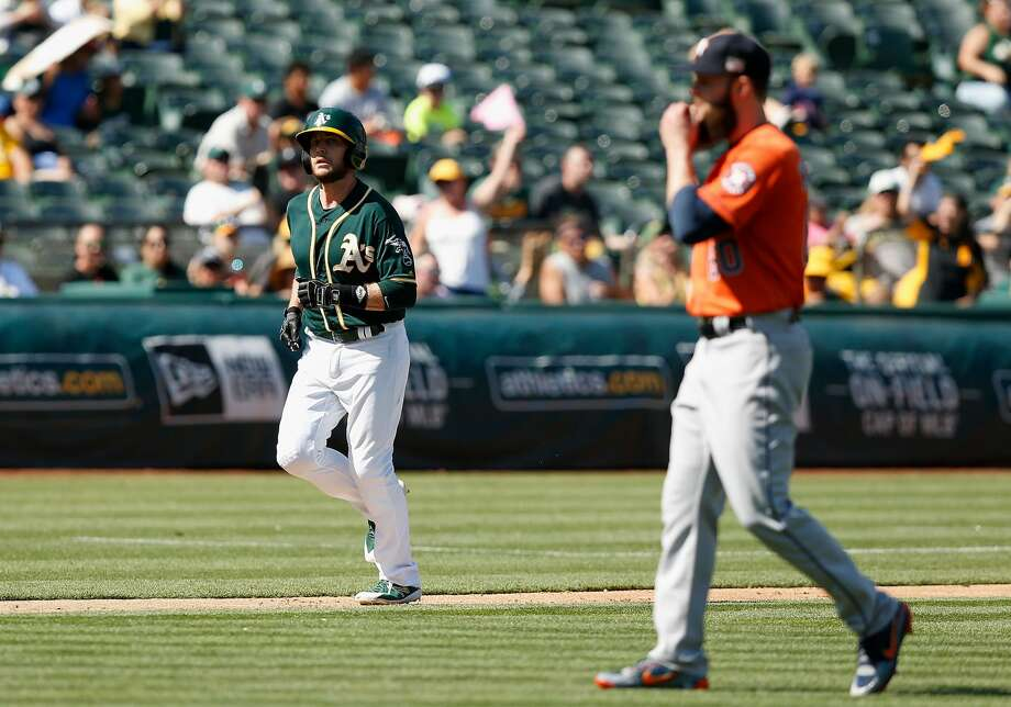 OAKLAND, CA - SEPTEMBER 10: Jed Lowrie #8 of the Oakland Athletics walks to home plate to score after pitcher Dallas Keuchel (right) #60 of the Houston Astros walked Matt Chapman #26 of the Oakland Athletics with bases loaded in the sixth inning at Oakland Alameda Coliseum on September 10, 2017 in Oakland, California. (Photo by Lachlan Cunningham/Getty Images) Photo: Lachlan Cunningham/Getty Images