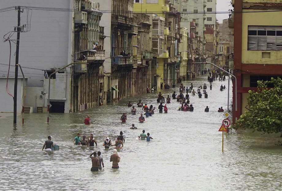 People move through flooded streets in Havana after the passage of Hurricane Irma, in Cuba, Sunday, Sept. 10, 2017. The powerful storm ripped roofs off houses, collapsed buildings and flooded hundreds of miles of coastline after cutting a trail of destruction across the Caribbean. Cuban officials warned residents to watch for even more flooding over the next few days. (AP Photo/Ramon Espinosa) Photo: Ramon Espinosa, STF / Associated Press / Copyright 2017 The Associated Press. All rights reserved.