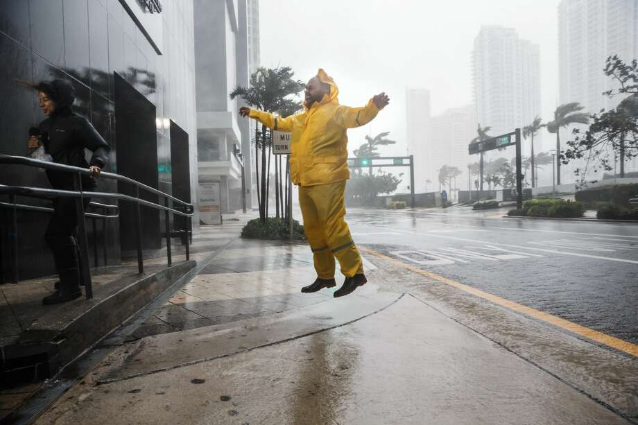 Weather reporters jump and cling on to illustrate the force of the winds caused by Hurricane Irma as it arrives in Miami, Fla., on Sept. 10, 2017.  Photo: Marcus Yam/LA Times Via Getty Images