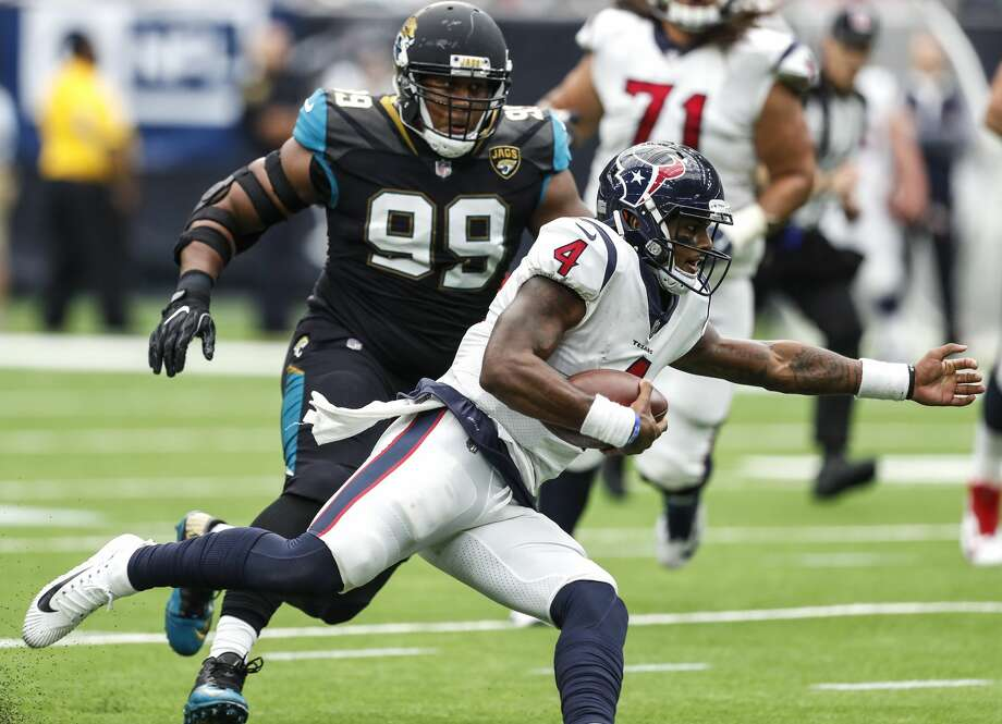 Texans quarterback Deshaun Watson (4) is chased out of the pocket by Jaguars defensive tackle Eli Ankou (99) during the fourth quarter Sunday. Photo: Brett Coomer/Houston Chronicle