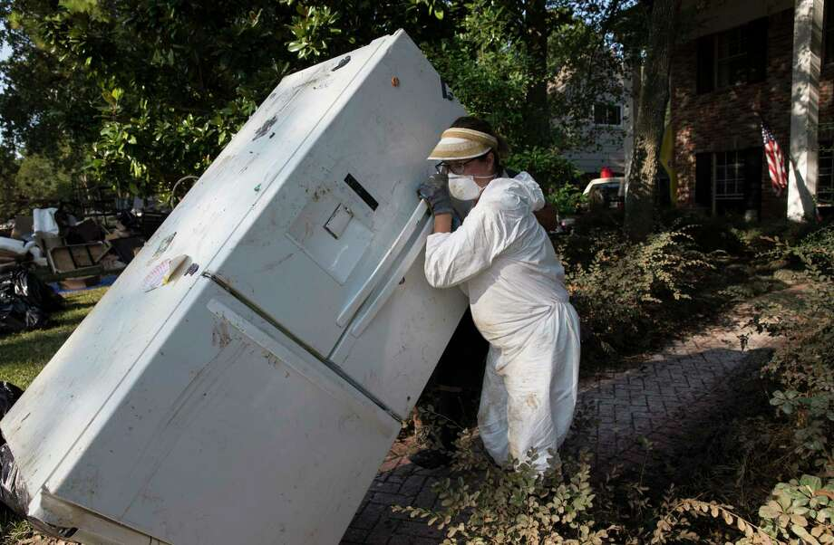 Jenna O'Neal moves a flood damaged refrigerator from her sister-in-law's house on Hickory Post Lane of Nottingham Forest Saturday. Photo: Yi-Chin Lee, Staff / © 2017  Houston Chronicle