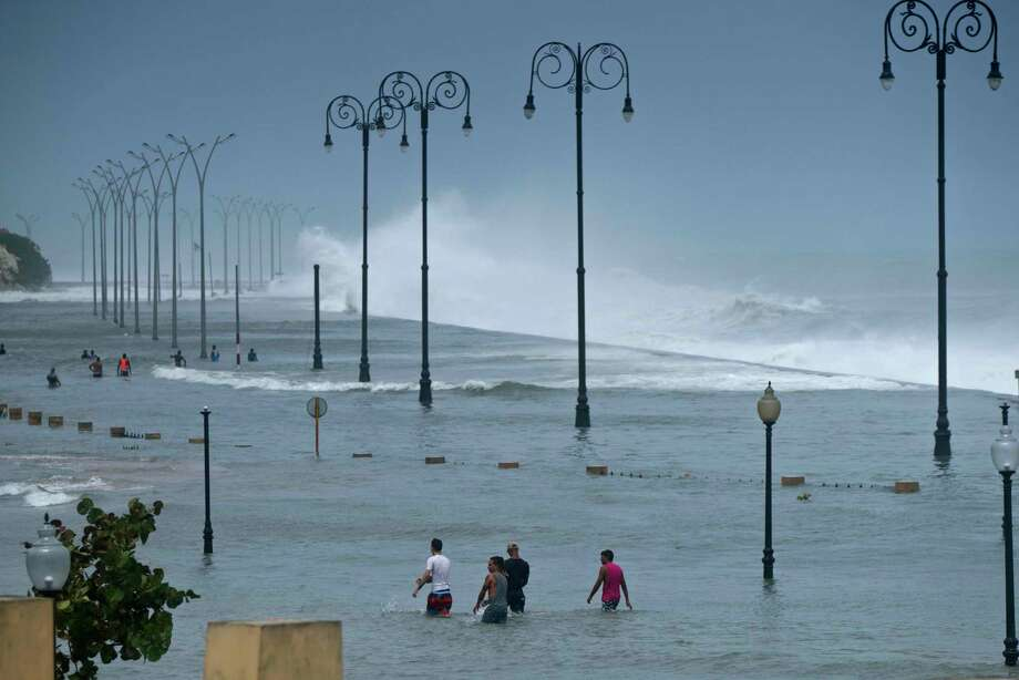 Residents walk on Havana's sea wall as the ocean crashes into it, after the passing of Hurricane Irma in Havana, Cuba, Sunday, Sept. 10, 2017. The powerful storm ripped roofs off houses, collapsed buildings and flooded hundreds of miles of coastline after cutting a trail of destruction across the Caribbean.There were no immediate reports of deaths in Cuba, a country that prides itself on its disaster preparedness, but authorities were trying to restore power and clear roads. (AP Photo/Ramon Espinosa) Photo: Ramon Espinosa, STF / Copyright 2017 The Associated Press. All rights reserved.