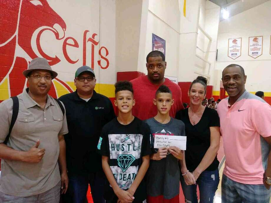 Jim Hicks (left) of RCS Sports presents an envelope stuffed with around $1,100 to one of the five families that benefited from Saturday's #HealingFromHarvey charity basketball event. Hicks said the event was first and foremost about giving back, and secondarily about basketball, and he stated that as more people are starting to question where their Harvey Relief donations are going and how they're used, it's special to be able to see and shake hands with the families being helped. Photo: Rick Godfrey