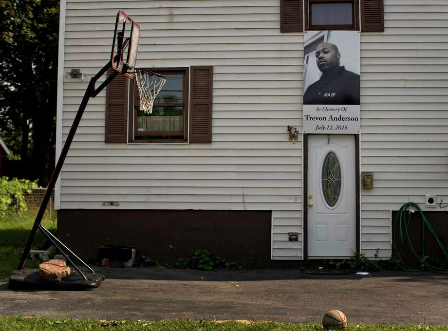 A photo of a victim of gun violence hangs over the entrance to a home, Monday, Aug. 21, 2017, in the South Side neighborhood of Syracuse, N.Y. From 2014 through this past June, 48 youths aged 12 to 17 in Syracuse were killed or injured in gun violence. The city's rate of teen shootings per capita is more than double those seen in the vast majority of U.S. cities with populations of 50,000 or more, according to an Associated Press and USA TODAY Network analysis of shooting cases compiled by the nonprofit Gun Violence Archive. (AP Photo/Julie Jacobson) ORG XMIT: NY928 Photo: Julie Jacobson / Copyright 2017 The Associated Press. All rights reserved.