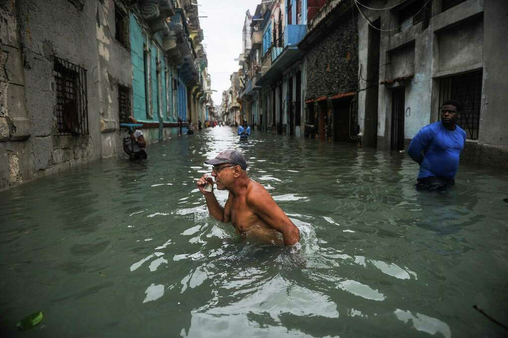 Havana devastated after storm times union topshot a cuban wades through a flooded street in havana on september 10 stopboris Gallery