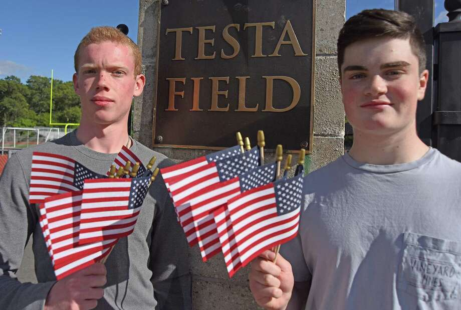 Norwalk High senior athletes Colin Baker, left, and Bobby Gummer displayed some of the 2,996 flags they intend to plant on school grounds to honor the victims of 9/11 on Monday. Photo: John Nash / Hearst Connecticut Media / Norwalk Hour