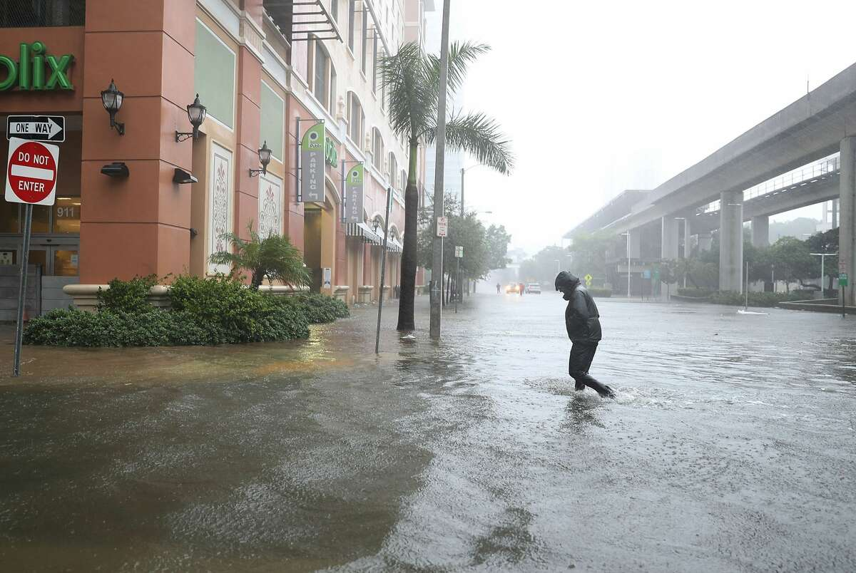 A person walks through a flooded street in the Brickell area of downtown as Hurricane Irma passes through on Sept. 10, 2017 in Miami, Florida. Hurricane Irma made landfall in the Florida Keys as a Category 4 storm on Sunday, lashing the state with 130 mph winds as it moves up the coast.