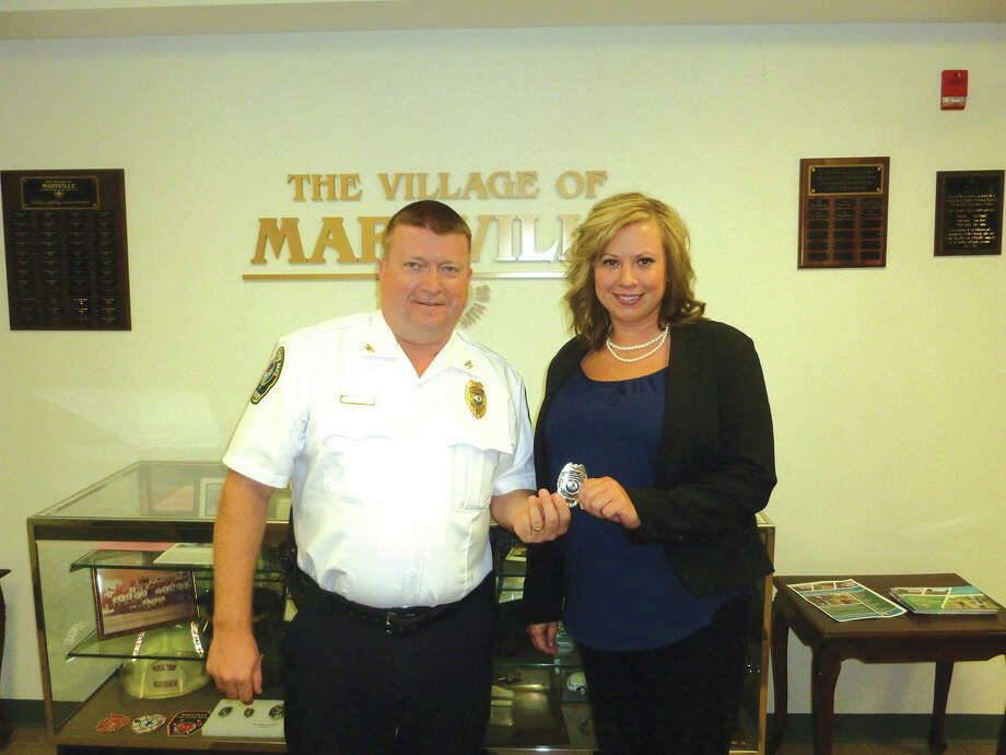 Maryville Police Chief Rob Carpenter presents a badge to newly-hired patrol officer Crissy Murphy at Wednesday's Maryville Village Board meeting. Photo: John Sommerhof • Jsommerhof@edwpub.net