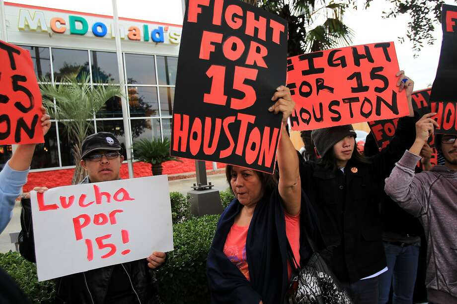 Ricky Quintana and Teresa Torres, 60, protest outside a McDonald's on Kirby near highway 59 with minimum wage workers and supporters in a national effort to demand higher living wage on Thursday, Dec. 5, 2013, in Houston. ( Mayra Beltran / Houston Chronicle ) Photo: Mayra Beltran, Houston Chronicle