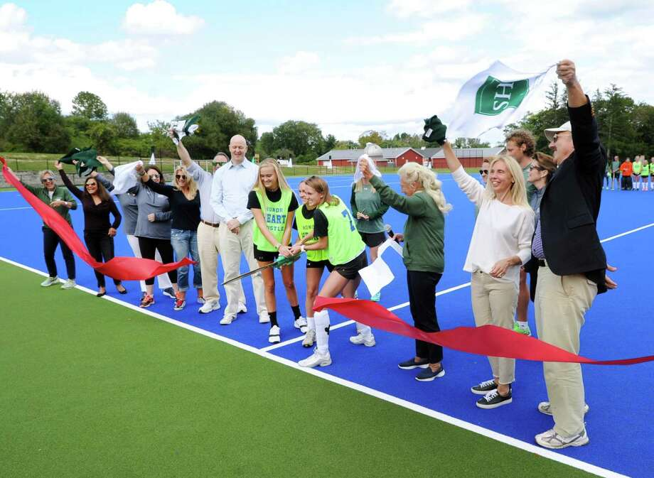 Sacred Heart Greenwich seniors and athletes in yellow shirts at center (from left to right) Olivia Monahan, Samantha Clark and Charlotte Sheehan cut the ribbon as school officials cheer them on during the dedication of the Magnetti and Sheehan Athletic Fields at Sacred Heart Greenwich in Greenwich, Conn., Friday, Sept. 8, 2017. Photo: Bob Luckey Jr. / Hearst Connecticut Media / Greenwich Time