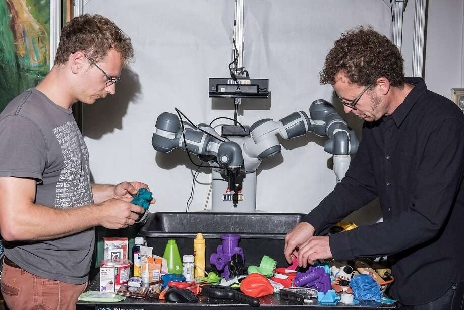 Jeff Mahler (left) and Ken Goldberg arrange objects for a robot to grasp at UC Berkeley. The techniques they're using to train the robot represent a fundamental shift in robotics research. Photo: JASON LECRAS, NYT