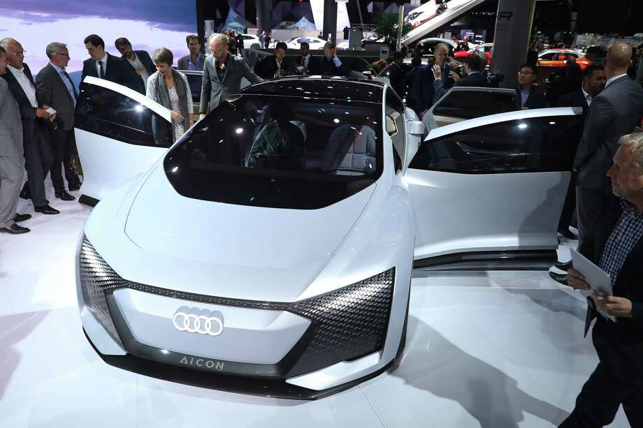 Journalists look at an Audi Aicon autonomous electric car at the Volkswagen Preview Night prior to the 2017 Frankfurt Auto Show