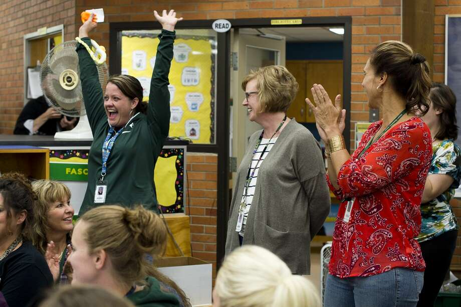 Siebert Elementary teacher Megan Storm throws her hands into the air as fellow Siebert teacher Amy Burks is awarded four Caribbean vacations after being nominated by Storm for a contest hosted by CheapCaribbean.com in celebration of National Teacher Appreciation Day on Friday, September 8, 2017 at Siebert Elementary. (Katy Kildee/kkildee@mdn.net) Photo: (Katy Kildee/kkildee@mdn.net)