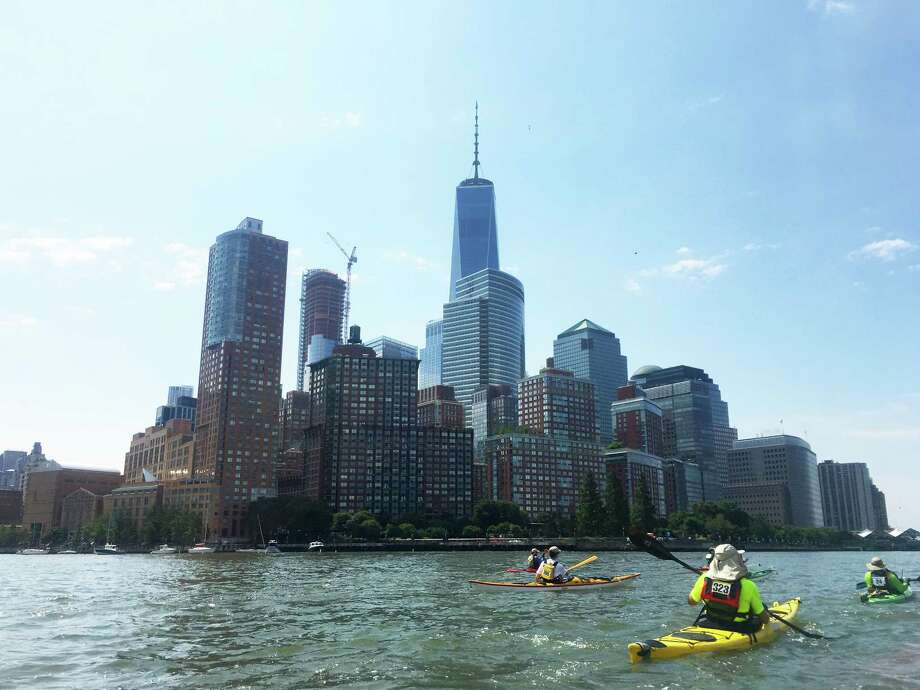 Kayakers approach the lower end of Manhattan on the Hudson River, where One World Trade Center dominates the skyline. Photo: Photo By David Brown For The Washington Post. / For The Washington Post