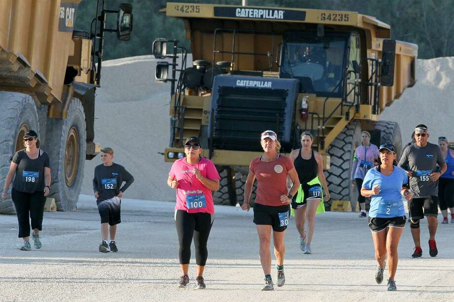 Runners pass by huge mining trucks as they make their way through the Quarry Crusher run at Vulcan Materials Company 1604 Quarry, 4303 N. Loop 1604 E, on Saturday, Sept. 9, 2017.  MARVIN PFEIFFER/mpfeiffer@express-news.net Photo: Marvin Pfeiffer, Staff / San Antonio Express-News / Express-News 2017