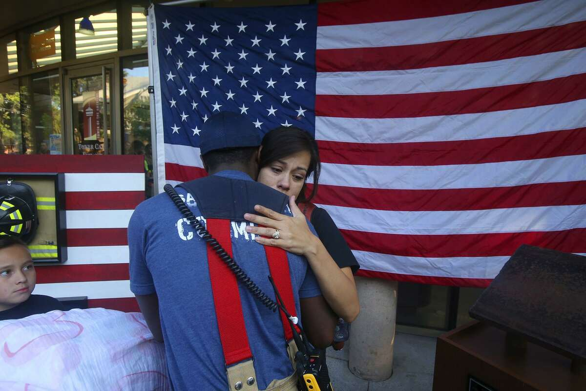 Jennifer Deem (center, facing) is hugged by Aaron Ward Monday September 11, 2017 during the San Antonio 110 9/11 Memorial Climb at the Tower of the Americas in San Antonio, Texas. Jennifer Deem is the widow of fallen San Antonio firefighter Scott Patrick Deem who lost his life last May while searching for potential victims during a structure fire. First responders including firefighters and police climbed the Tower of the Americas to honor fallen firefighters from the 911 tragedy in New York City.