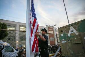 Firefighter Dave Crespin raises a flag to half staff to during a ceremony to commemorate the firefighters who perished in the 9/11 attacks at Fire Station 7 in San Francisco, Calif., on Monday, Sept. 11, 2017.