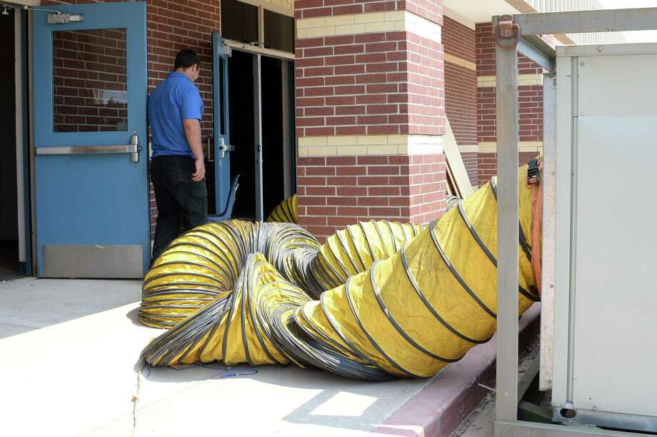 Workers install dehydration equipment to deal with flood damage at Creech Elementary School in Katy on Sept. 6, 2017. Photo: Craig Moseley, Staff / ©2017 Houston Chronicle