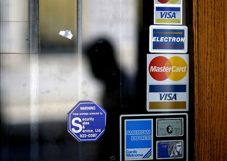 FILE - In this July 18, 2012, file photo, a pedestrian walks past credit card logos posted on a downtown storefront in Atlanta. On Monday, Sept. 11, 2017, Equifax said it has made changes to address customer complaints since it disclosed a week earlier that it exposed vital data on about 143 million Americans. Equifax has come under fire from members of Congress, state attorneys general, and people who are getting conflicting answers about whether their information was stolen. Equifax is trying again to clarify language about people�s right to sue, and said Monday it has made changes to address customer complaints. (AP Photo/David Goldman, File) Photo: David Goldman, Associated Press