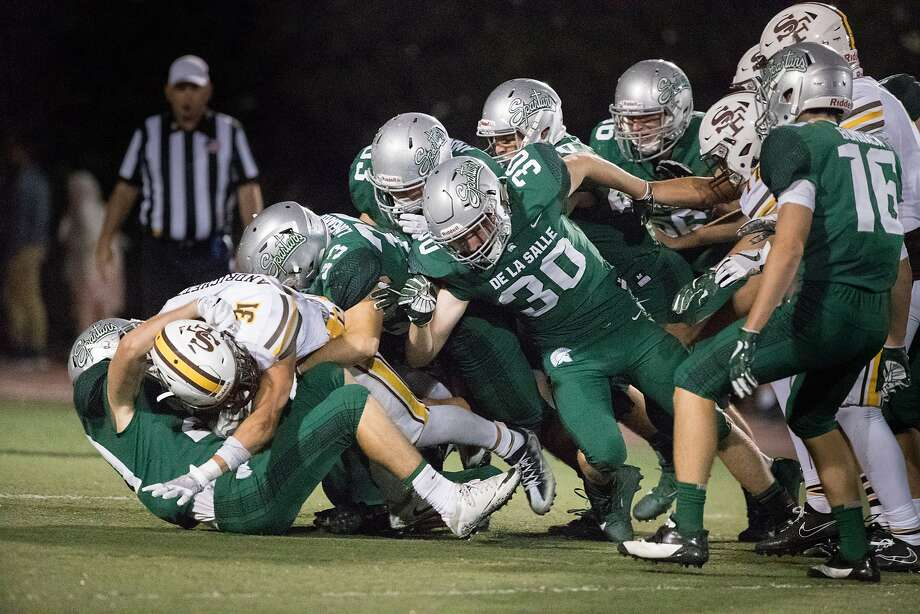 De La Salle Jacob Huckelberry (30) and a host of teammates tackle St. Francis runner Lucas Andrighetto (31) in the second half of the Spartans' 31-7 victory in Concord on Friday. Photo: Paul Kuroda, Special To The Chronicle