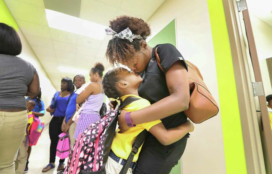 First-grader Jordain Hicks gives her mother Brittney Harvey a kiss before the start of school at Codwell Elementary Monday, Sept. 11, 2017, in Houston. Monday was the first day of school as hundreds of thousands of Houston area students have returned to their campuses since Hurricane Harvey devastated the region beginning on Aug. 26. Photo: Steve Gonzales, Houston Chronicle / © 2017 Houston Chronicle