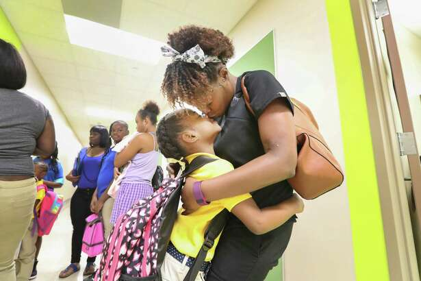 First-grader Jordain Hicks gives her mother Brittney Harvey a kiss before the start of school at Codwell Elementary Monday, Sept. 11, 2017, in Houston. Monday was the first day of school as hundreds of thousands of Houston area students have returned to their campuses since Hurricane Harvey devastated the region beginning on Aug. 26.