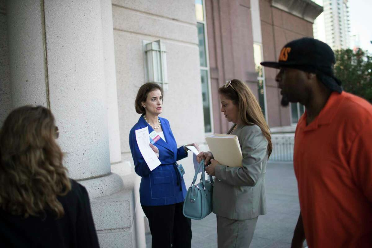 Judge Sylvia Matthews, center, provide a sheet with information about the changes made to the Harris County Criminal Court on front of the Civil Court, Monday, Sept. 11, 2017, in Houston.