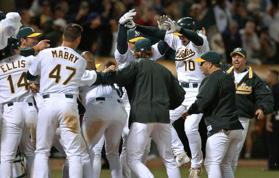 Oakland Athletics' Scott Hatteberg (10) jumps onto home plate and into the welcome of his teammates after hitting the game-winning home run off Kansas City Royals' Jason Grimsley in the ninth inning Wednesday, Sept. 4, 2002, in Oakland, Calif. The A's won 12-11 for their 20th consecutive victory, setting a new American League record. (AP Photo/Ben Margot) Photo: BEN MARGOT, AP