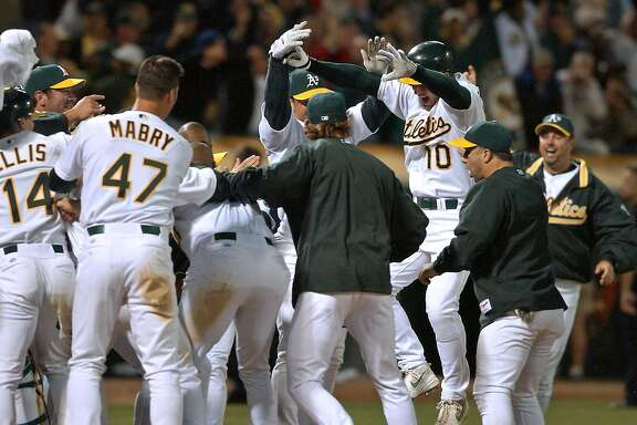Oakland Athletics' Scott Hatteberg (10) jumps onto home plate and into the welcome of his teammates after hitting the game-winning home run off Kansas City Royals' Jason Grimsley in the ninth inning Wednesday, Sept. 4, 2002, in Oakland, Calif. The A's won 12-11 for their 20th consecutive victory, setting a new American League record. (AP Photo/Ben Margot)