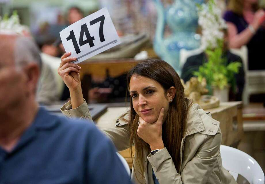 Kelly Ferguson shows her number after winning a bid during a Sunday morning auction on Sept. 10, 2017, in Houston. Ferguson, of Sugar Land, is in the real estate business but was at the auction shopping for herself.(Annie Mulligan / For the Houston Chronicle) Photo: Annie Mulligan, Freelance / @ 2017 Annie Mulligan