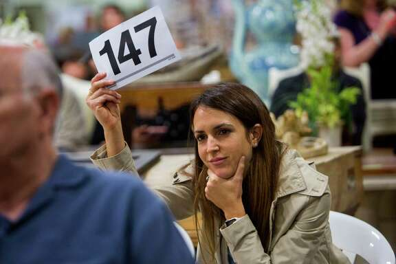 Kelly Ferguson shows her number after winning a bid during a Sunday morning auction on Sept. 10, 2017, in Houston. Ferguson, of Sugar Land, is in the real estate business but was at the auction shopping for herself.(Annie Mulligan / For the Houston Chronicle)